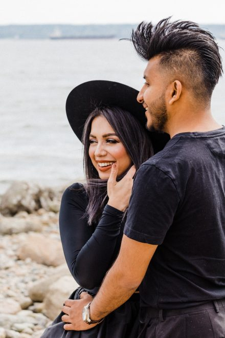 Couple dressed in black laughing on Vancouver beach