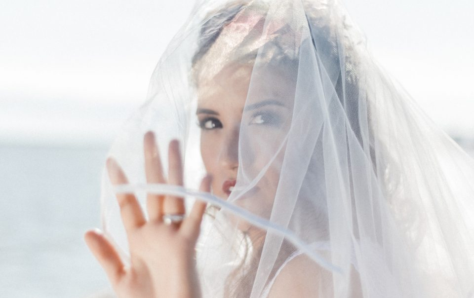 Portrait of a bride touching her veil