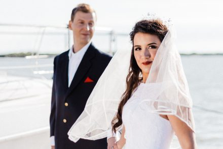 Portrait of a bride holding hand of groom, nautical themed wedding